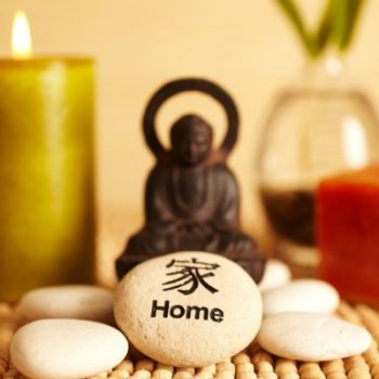 Spa still life buddha statue and river rock, bamboo in vase, and candles, and home river rock in Japanese characters