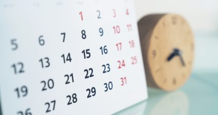 close up of calendar and clock on the table, planning for business meeting or travel planning concept